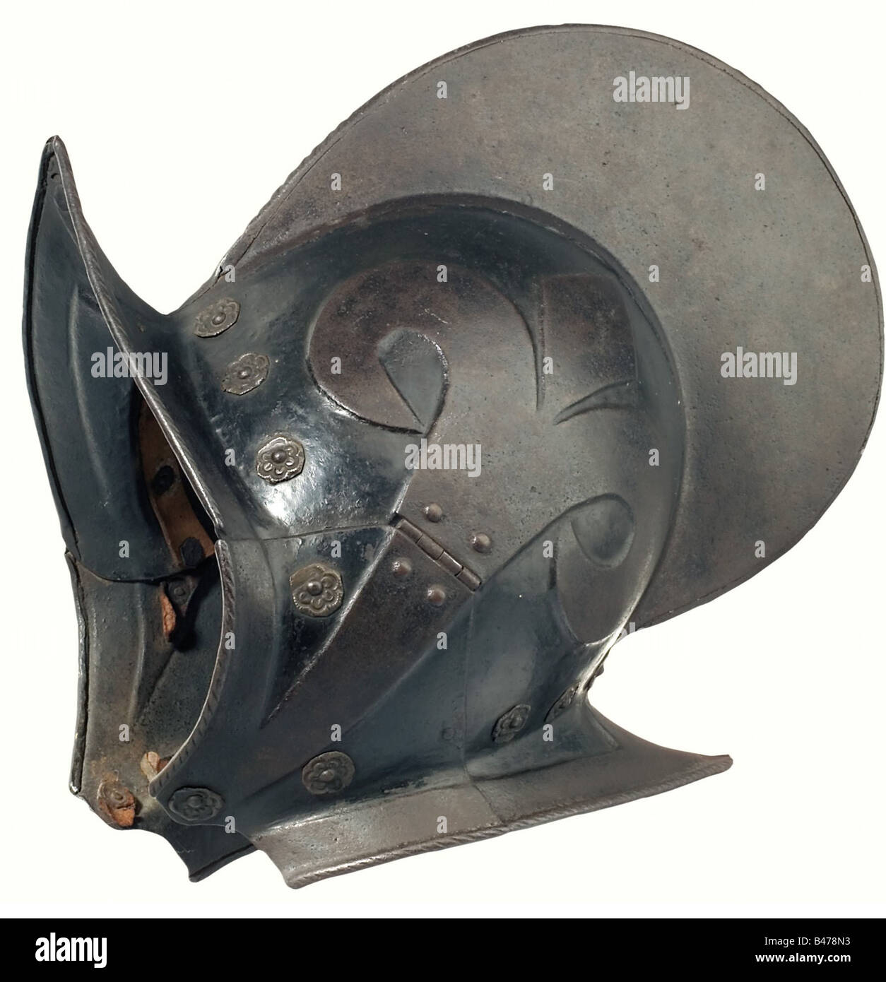 A morion with cheek pieces, German, end of the 16th century. Heavy two-piece forged skull with a high roped crest, - Stock Image