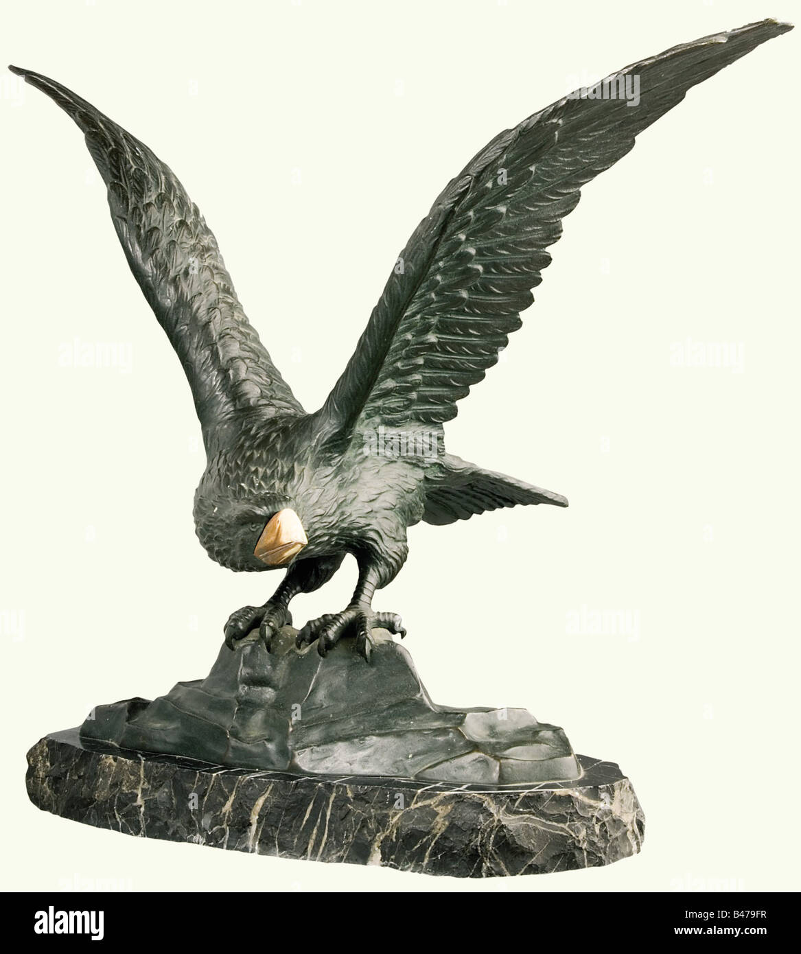 Rising eagle, a bronze figure, German, 19th century. With an inset ivory beak. The eagle is shown seated on a cliff, - Stock Image