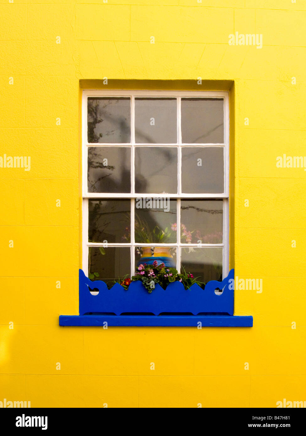 Bright blue window box beneath a window in a bright yellow wall - Stock Image