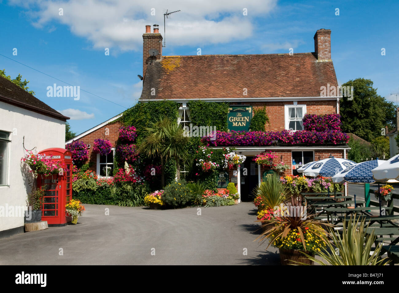 Typical English  pub in the summer time surrounded by summer flowers, located in Wimborne, Dorset, England, UK - Stock Image