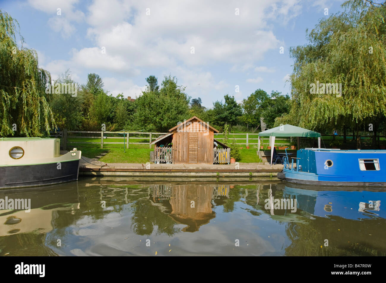 Waterside mooring with two boats and a chalet Grand union canal West London - Stock Image
