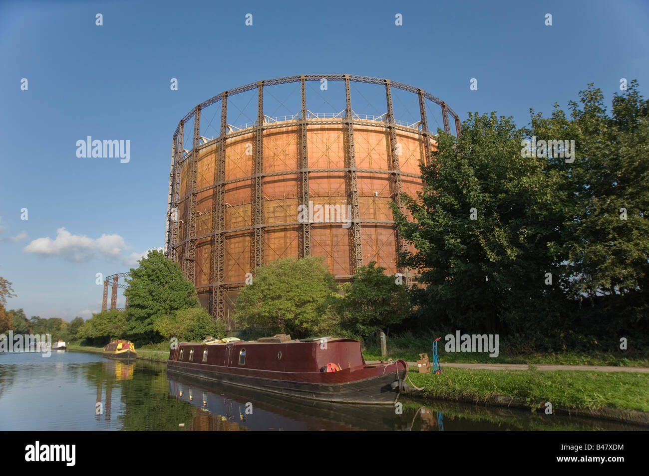 A house boat is moored beside an old Gas tower in the summer evening light on the grand Union can West London - Stock Image