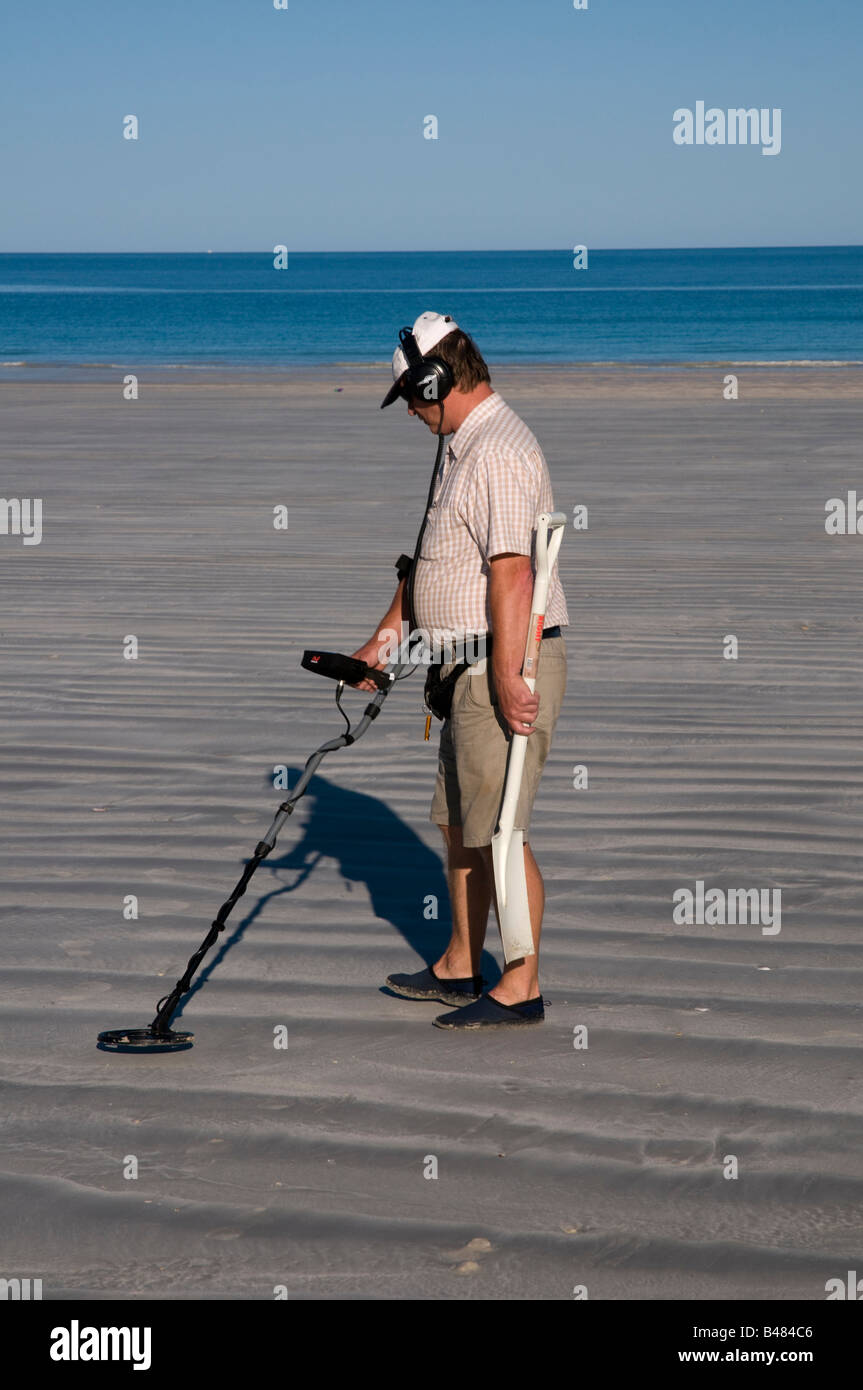 Man with metal detector and spade looking for lost objects on Cable Beache near Broome Western Australia - Stock Image