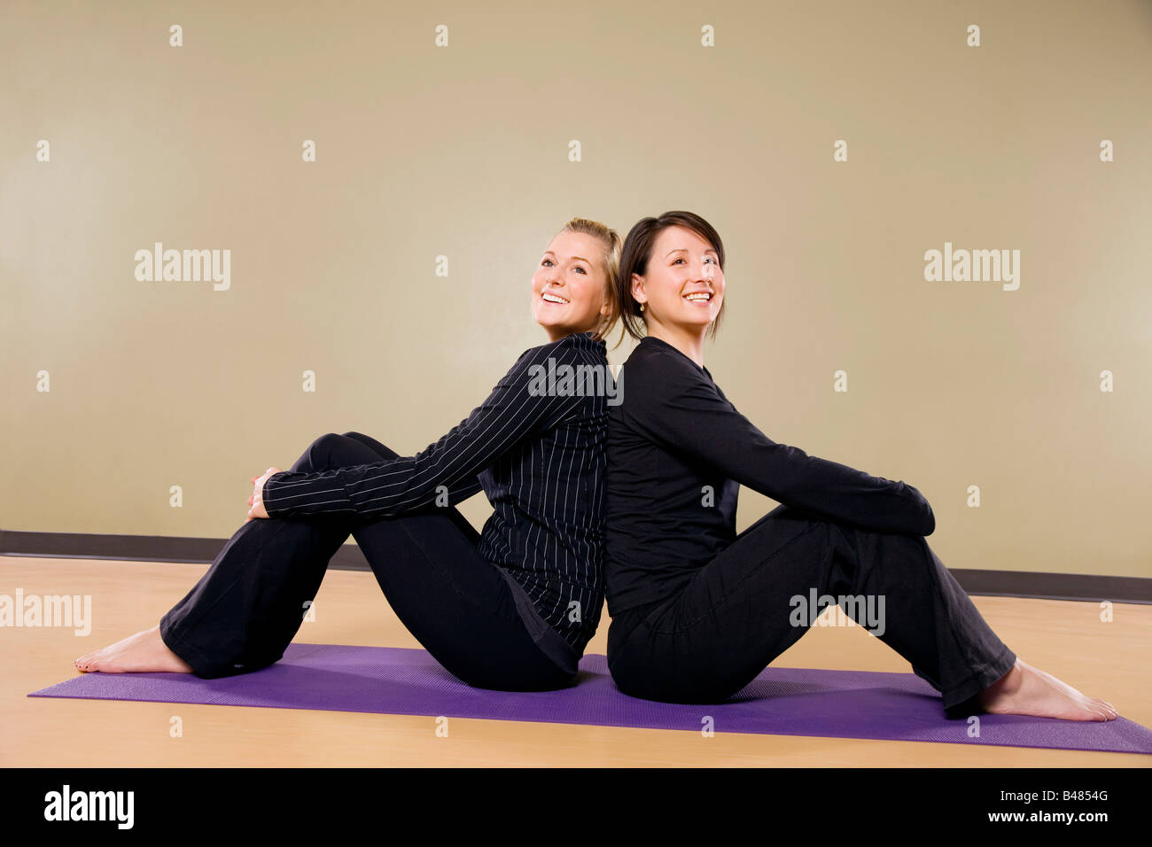 Two women sitting back to back Stock Photo
