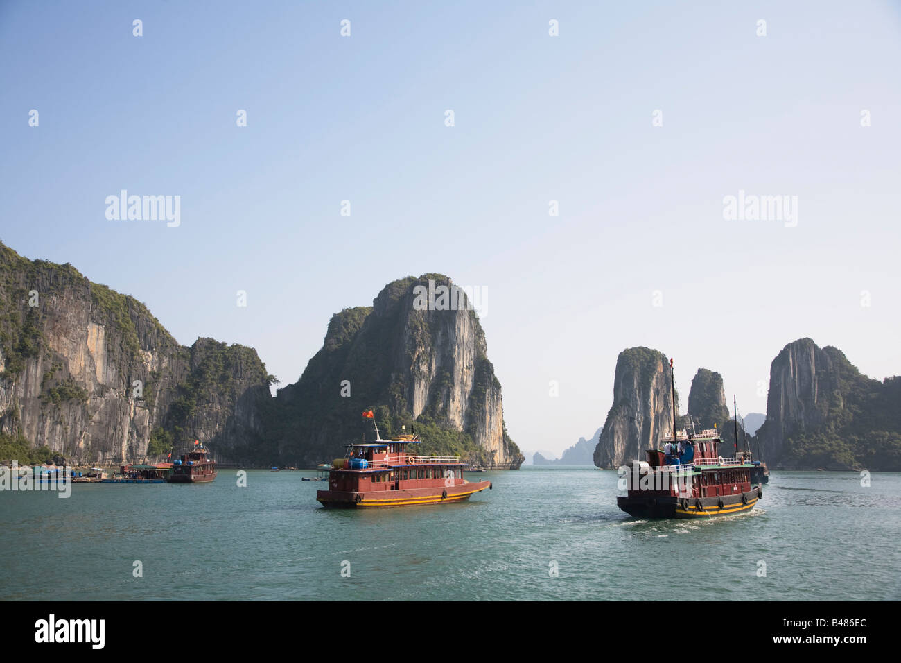 Junks and limestone karsts on the waters of Halong Bay, Vietnam - Stock Image