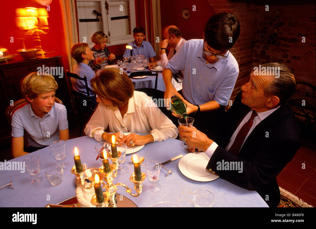 Boy pours water for a teacher during the evening meal - Stock Image