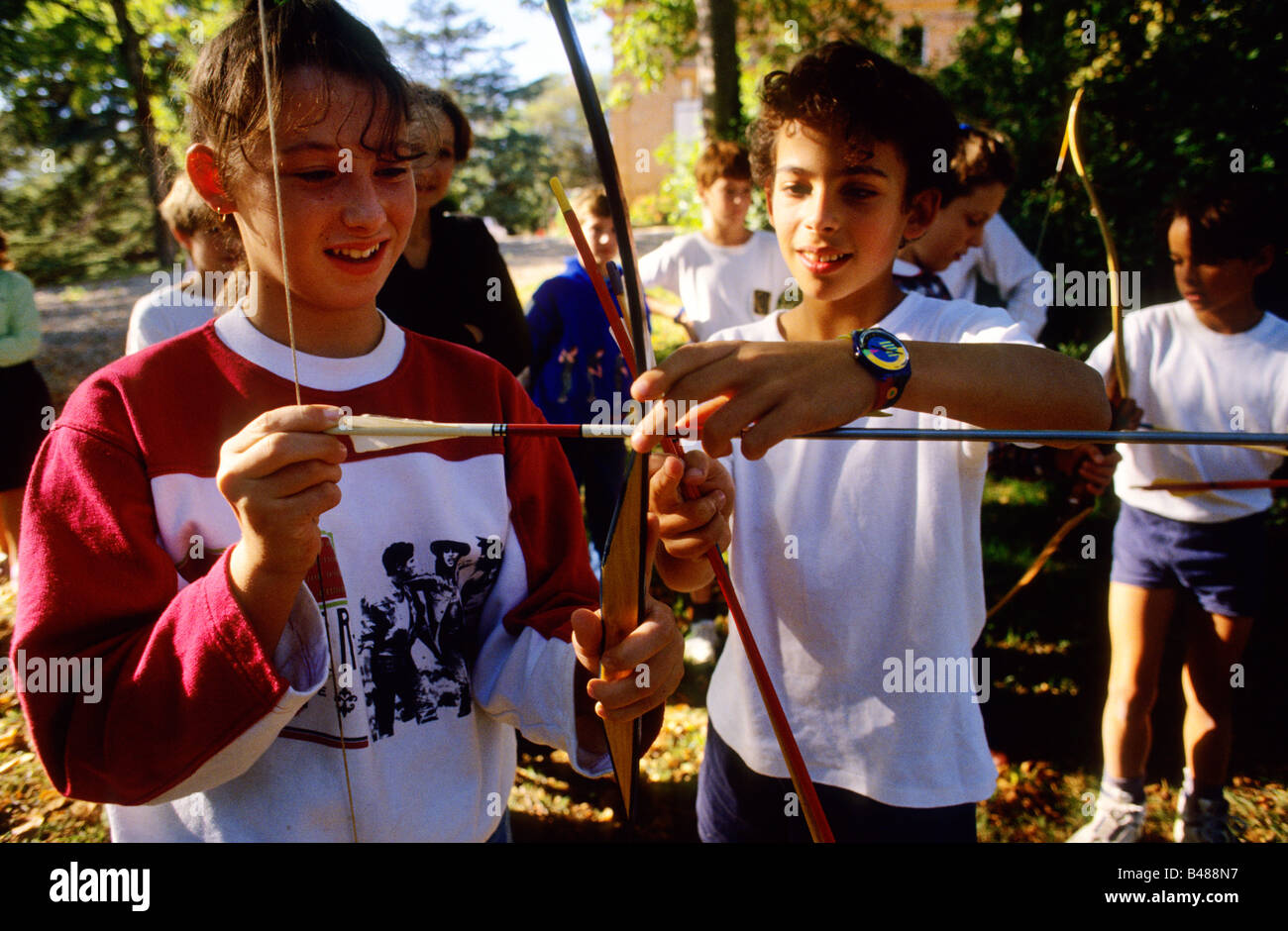 French girl from a local school near Toulouse leans archery from a boy at the Cothill School - Stock Image