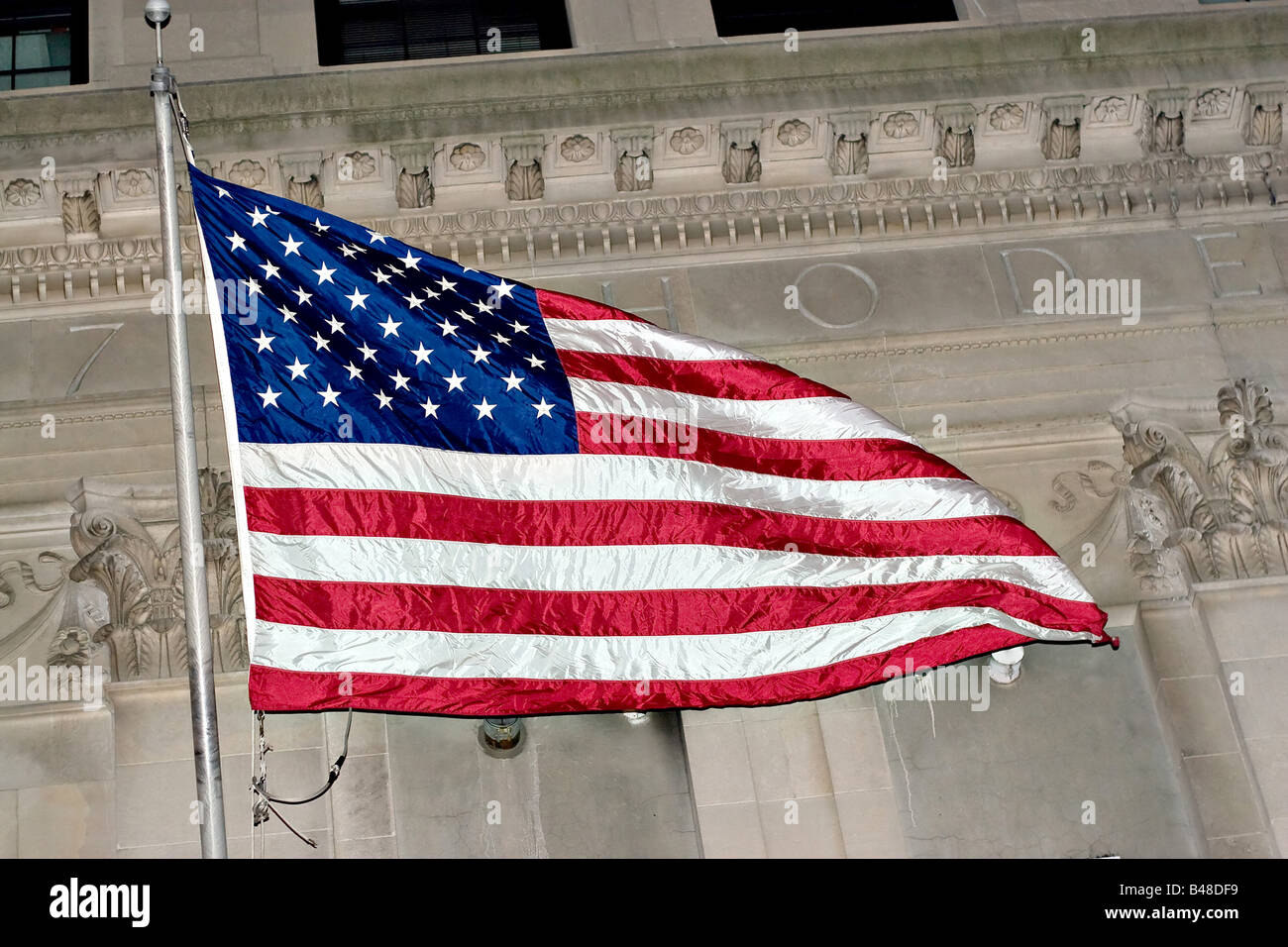 An American flag flying in front of some classic architecture - Stock Image