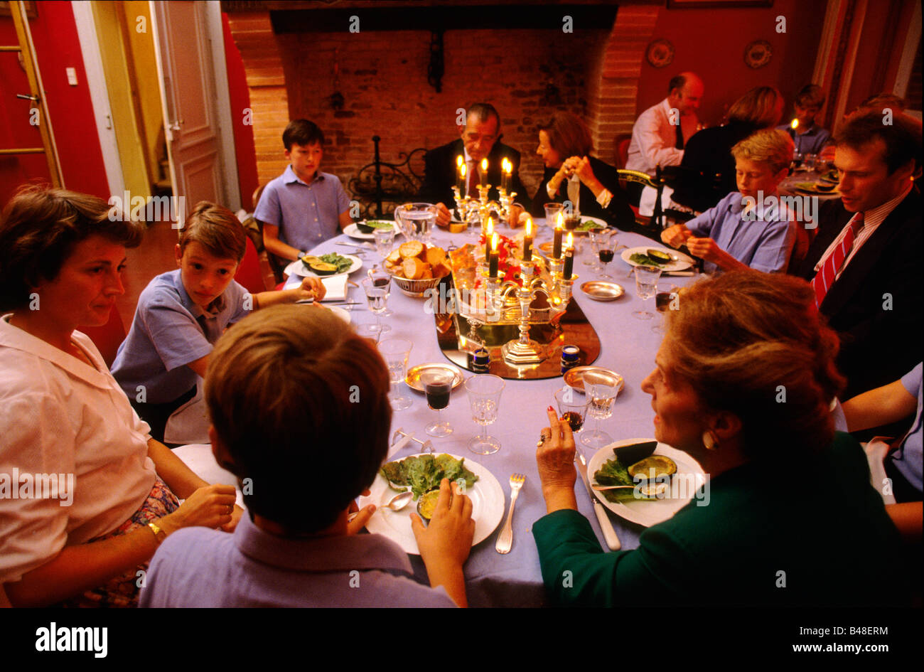 Teacher and pupils eating supper - Stock Image