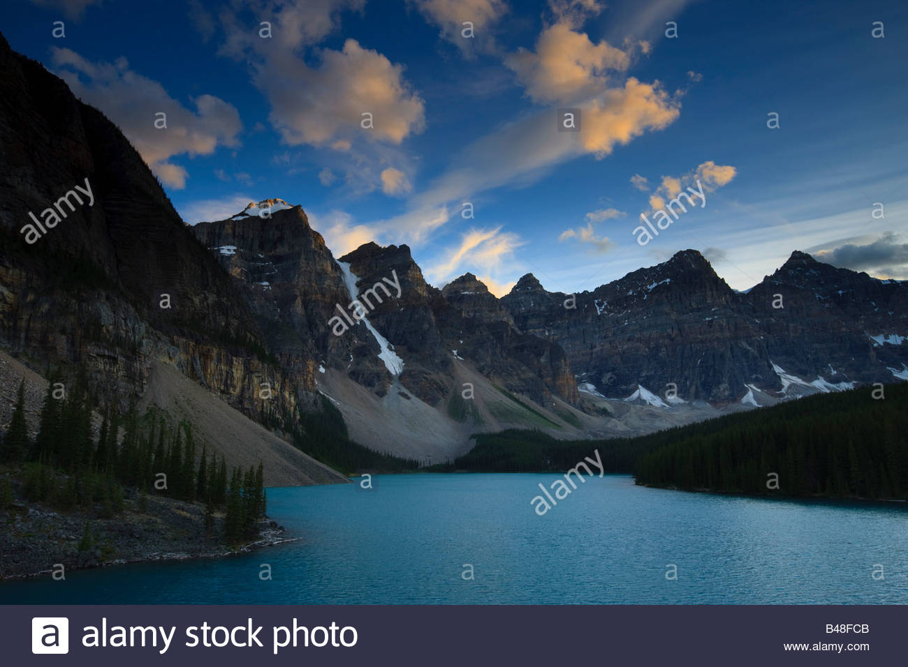 Strong winds blow cumulus clouds over the Canadian Rockies and Moraine Lake at sunset. - Stock Image