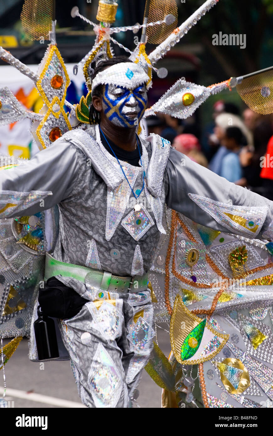 London , Notting Hill Carnival parade , handsome young black man with painted face & silver butterfly costume - Stock Image