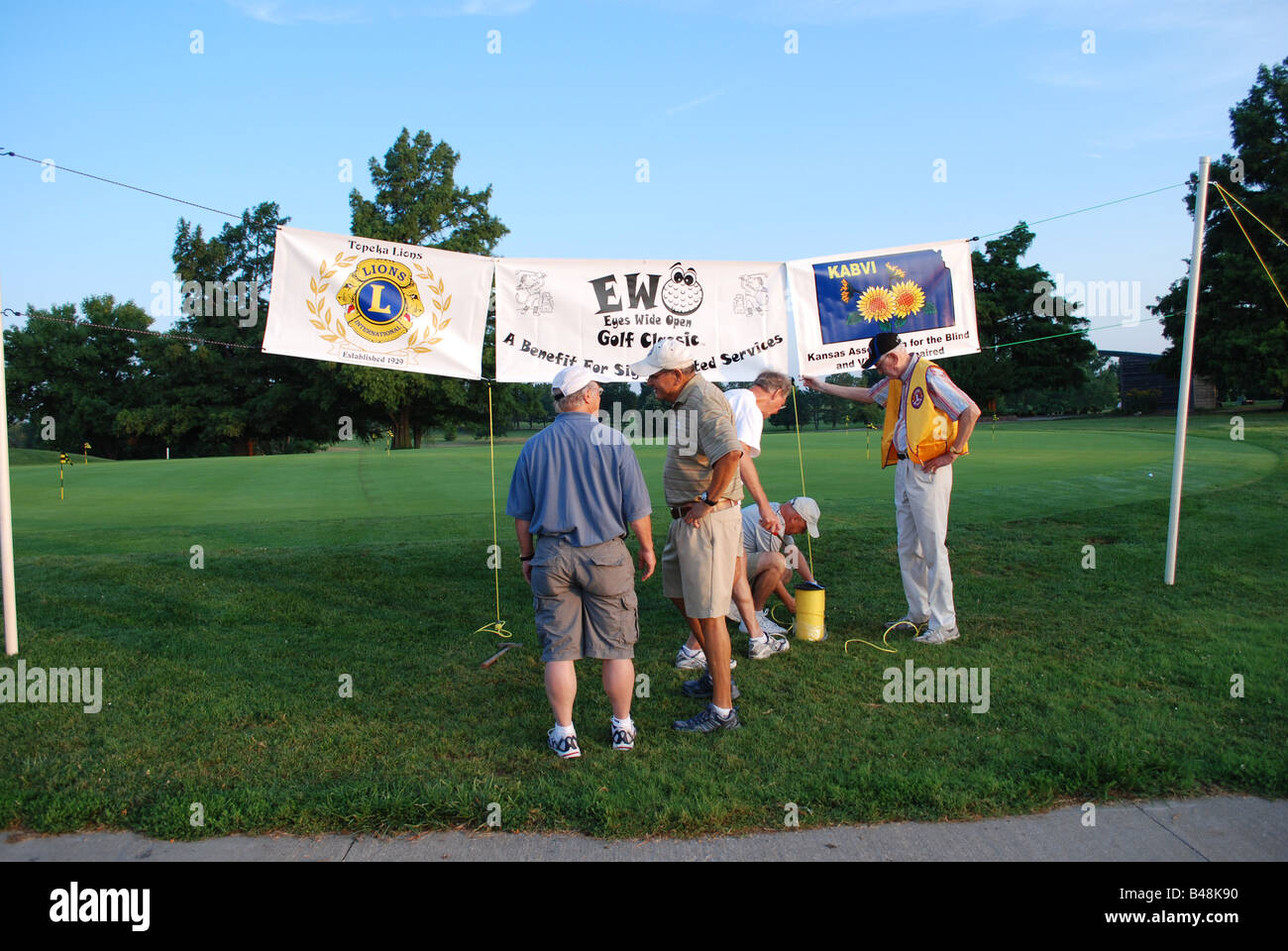 Lions Club member finish hanging the banners at the Lions Club Kansas Association for the Blind and Visually Impaired - Stock Image