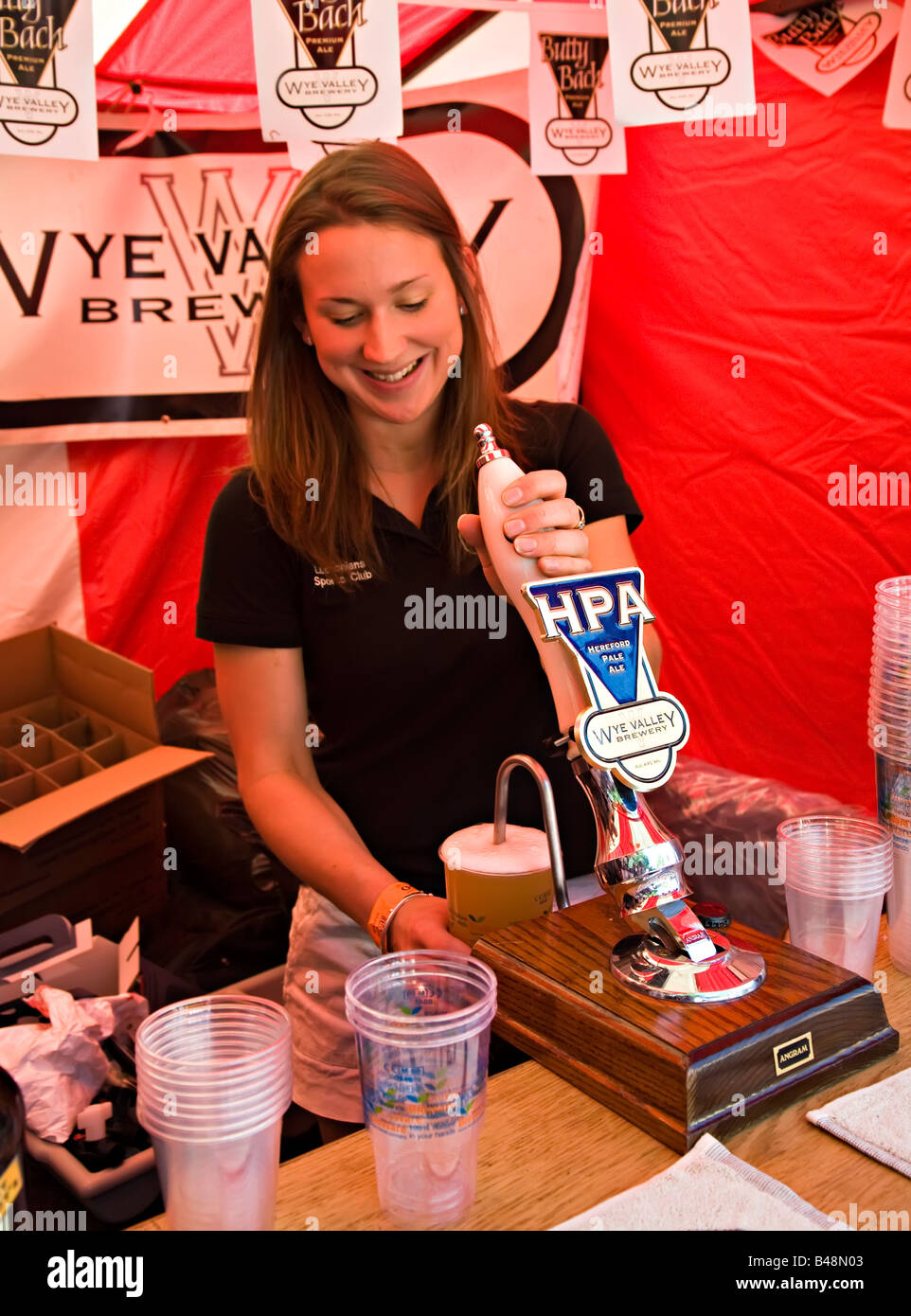 Girl pulling pint of beer in tent at Abergavenny Food Festival Wales UK - Stock Image