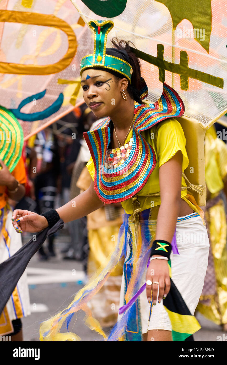 London , Notting Hill Carnival parade , pretty smiling happy exotic young  black girl dancer in Egyptian style fantasy - Stock Image