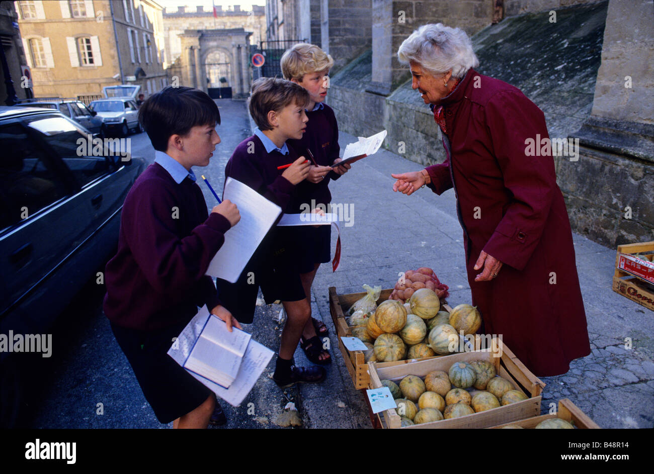 Boys try out their French in the local market - Stock Image