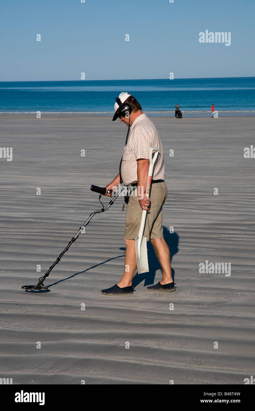 Man with metal detector and spade looking for lost objects on Cable Beach near Broome Western Australia - Stock Image