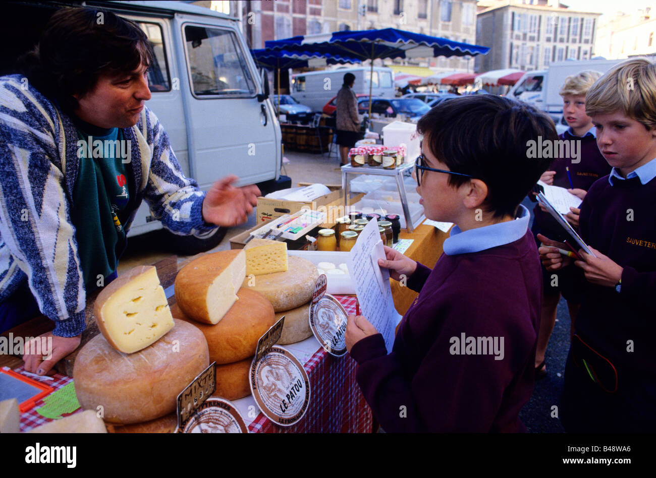 Boys try out their French at a cheese stall in the local market - Stock Image