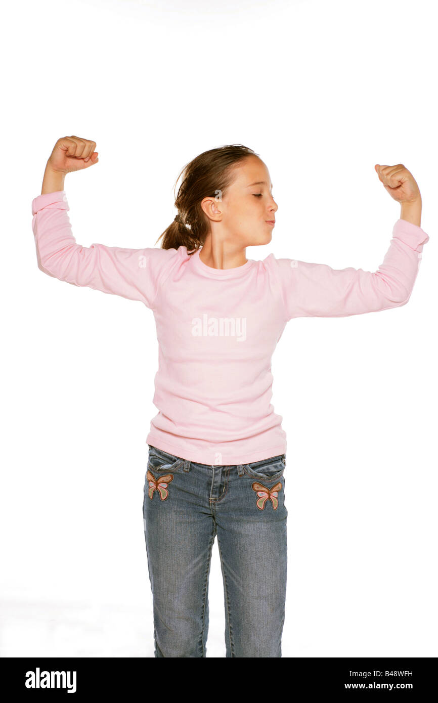 Stock Photo showing a Pre Teen Girl Making a Muscles with both arms using all her might - Stock Image