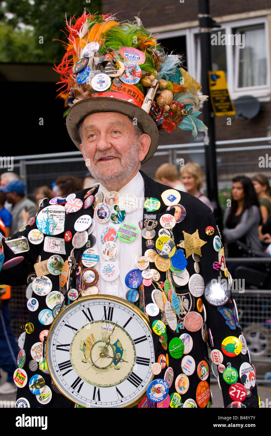 Notting Hill Carnival parade , elderly white man with beard dressed in top hat covered in badges and with a large - Stock Image