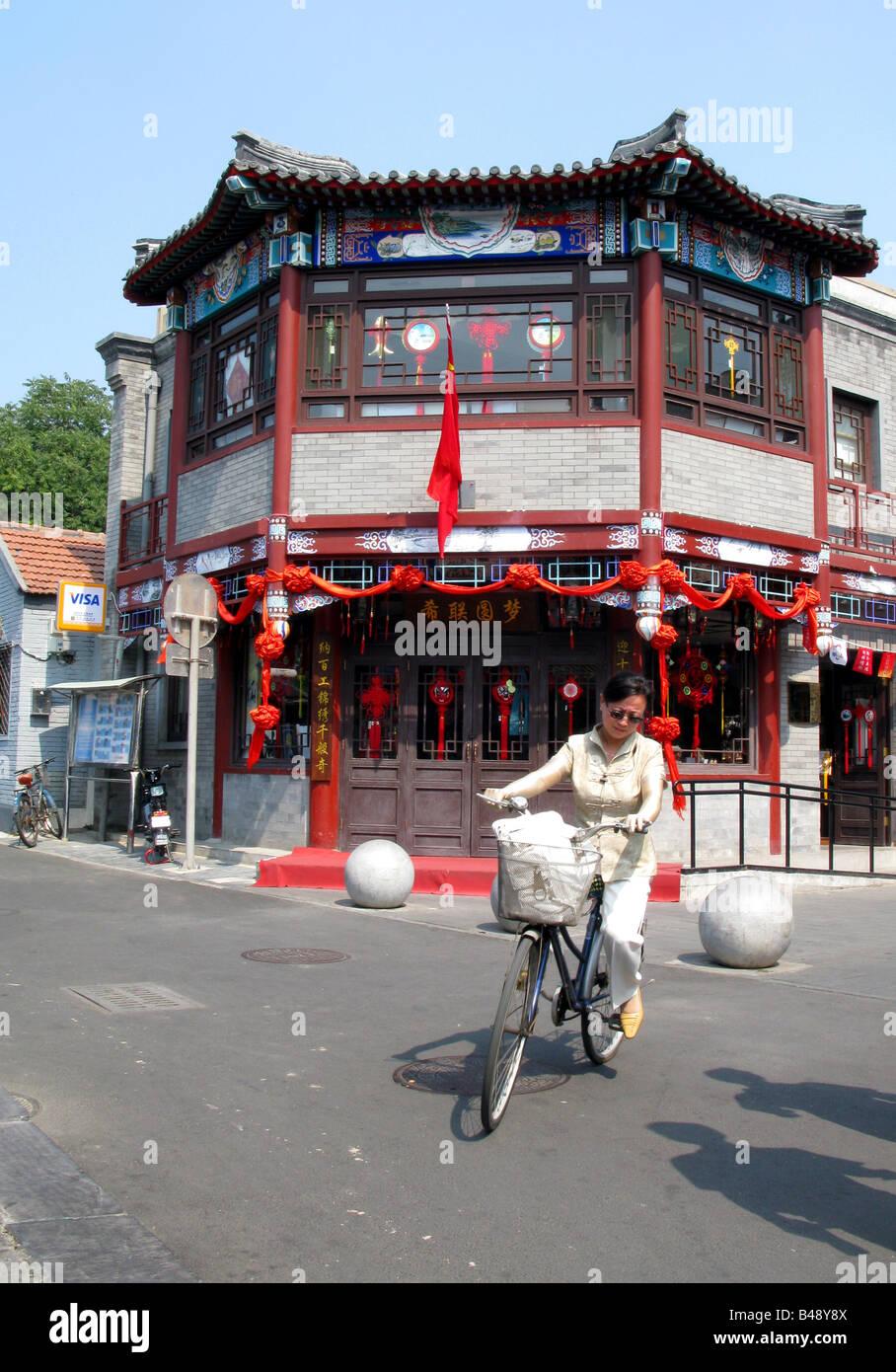 A women on a bike near Yinding bridge and Yandai Byway near Lake Qianhai and lake Houhai in the Shichahai district - Stock Image
