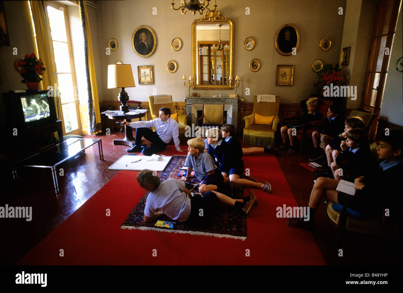 Boys watch a video with their teacher.The school has an annex at Saveterre Chateau near Toulouse, France. - Stock Image