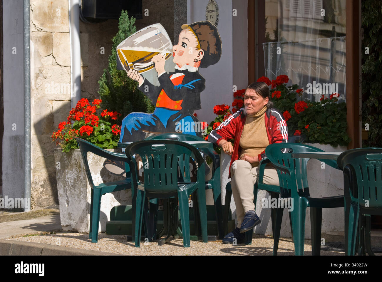Woman smoking outside French bar, sud-Touraine, France. - Stock Image