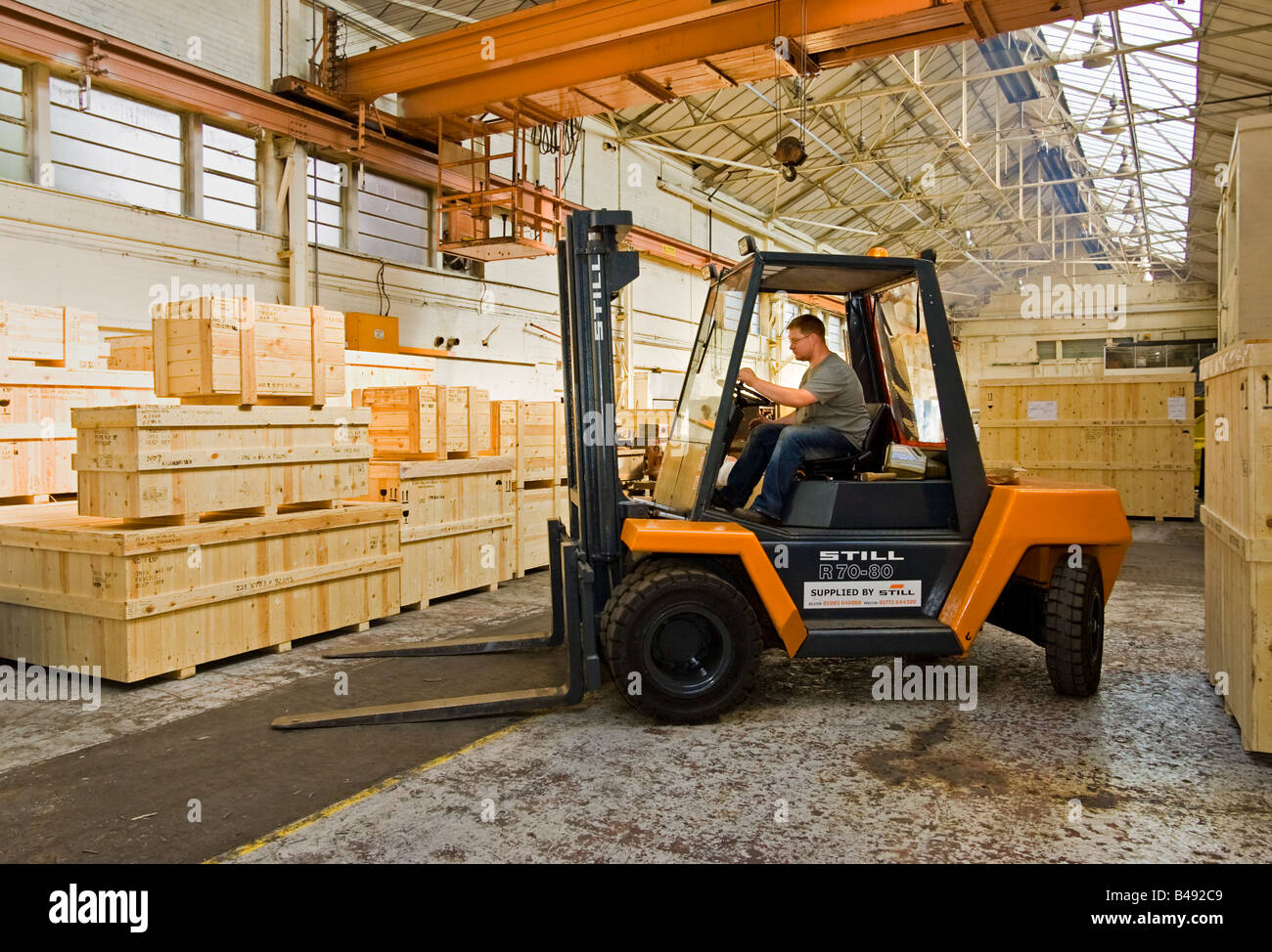 Warehouse - Man driving forklift truck, UK - Stock Image
