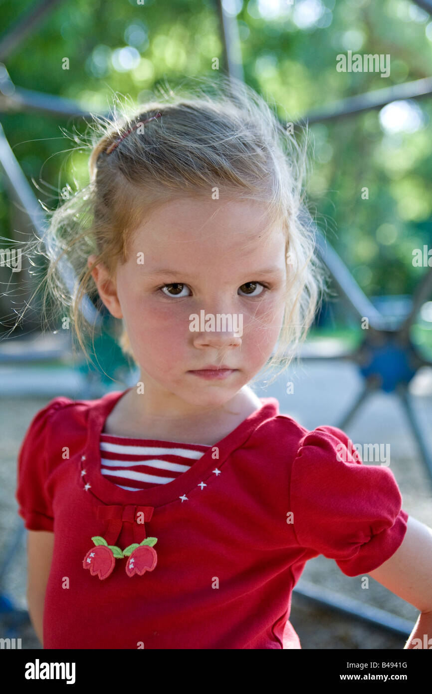 A girl at the park looks defiantly at the camera - Stock Image
