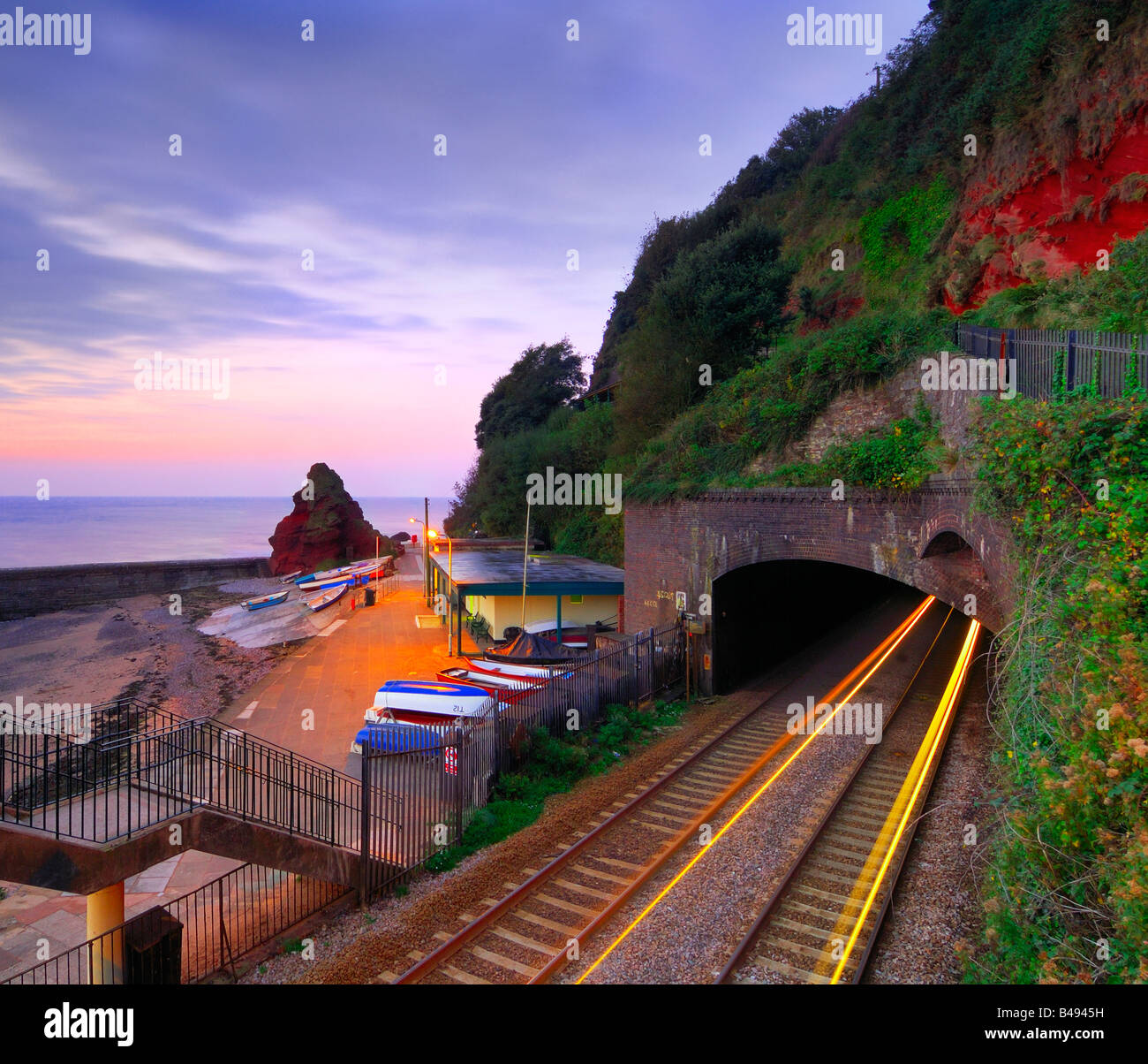 Sunrise from the railway footbridge at Dawlish in South Devon with the light trails of a train coming out of the - Stock Image