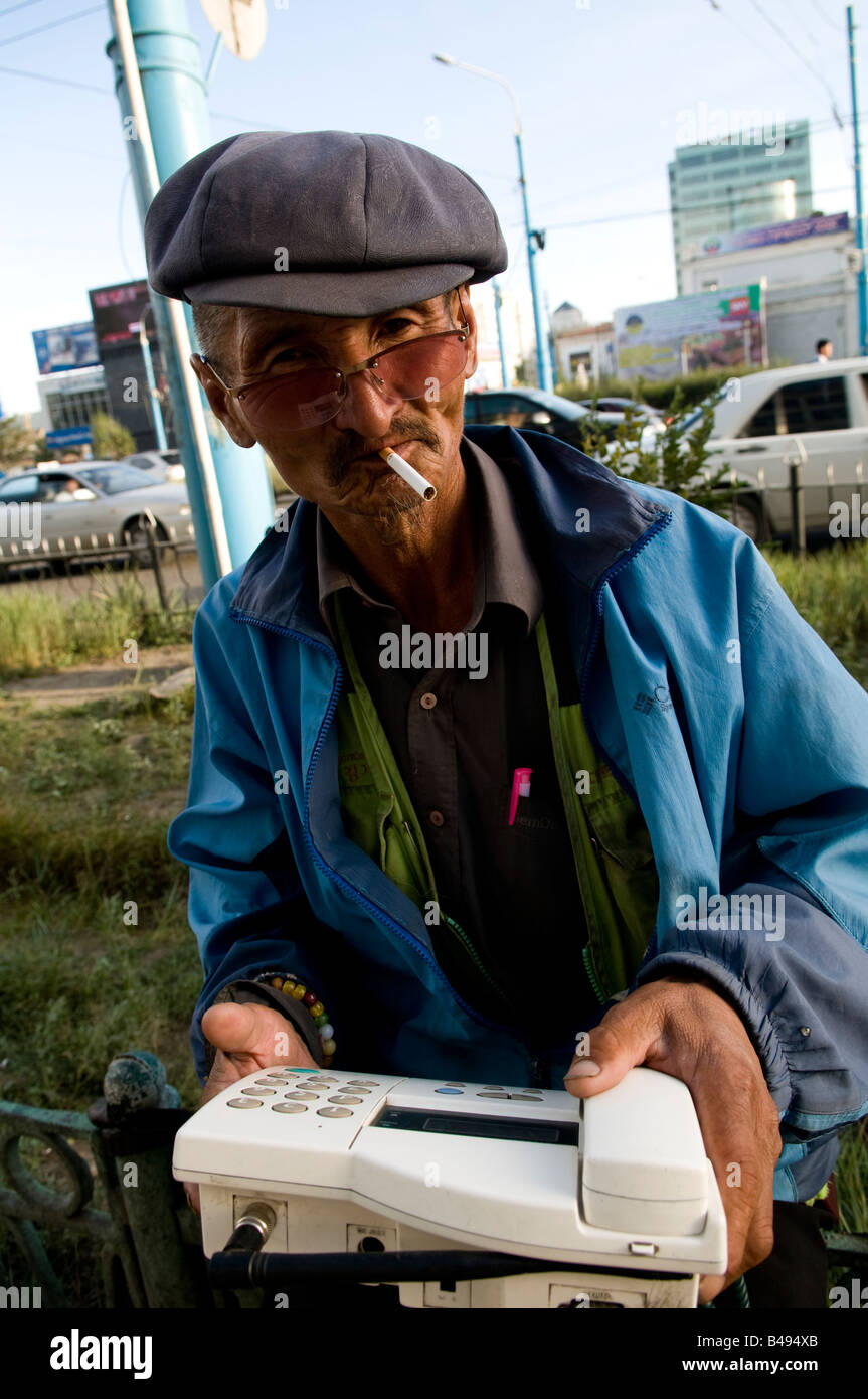 A Mongolian man with his public telephone in his hands. it is possible to make local calls through this cordless - Stock Image