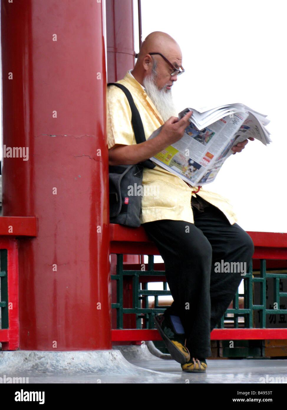 A bald man reads a newspaper in the Shichahai Hutong near Yinding Bridge in Beijing, China - Stock Image