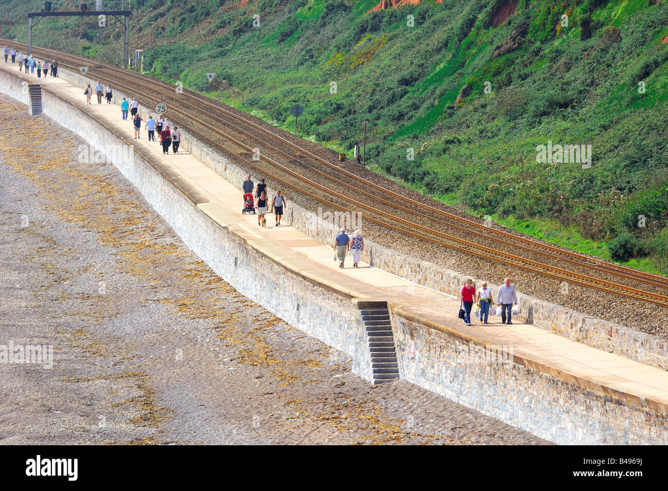 Tourists walking along the seafront promenade beside the railway track between Dawlish and Dawlish Warren in South - Stock Image