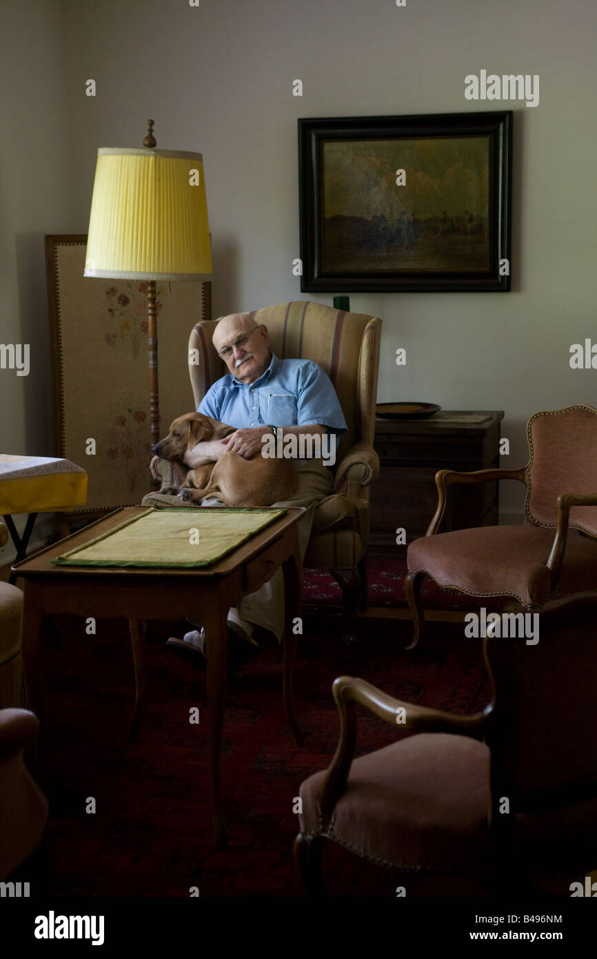 An old man comforts a dog he is holding on his lap inside a dark room with antique furniture. - Stock Image