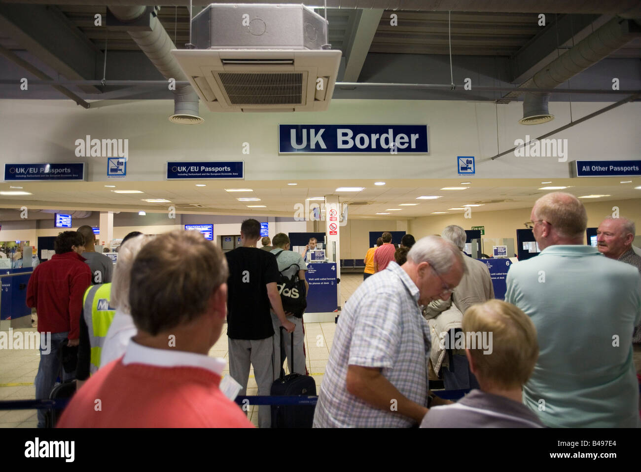 People queuing at immigration UK border, Luton Airport, England, Britain, Europe. - Stock Image