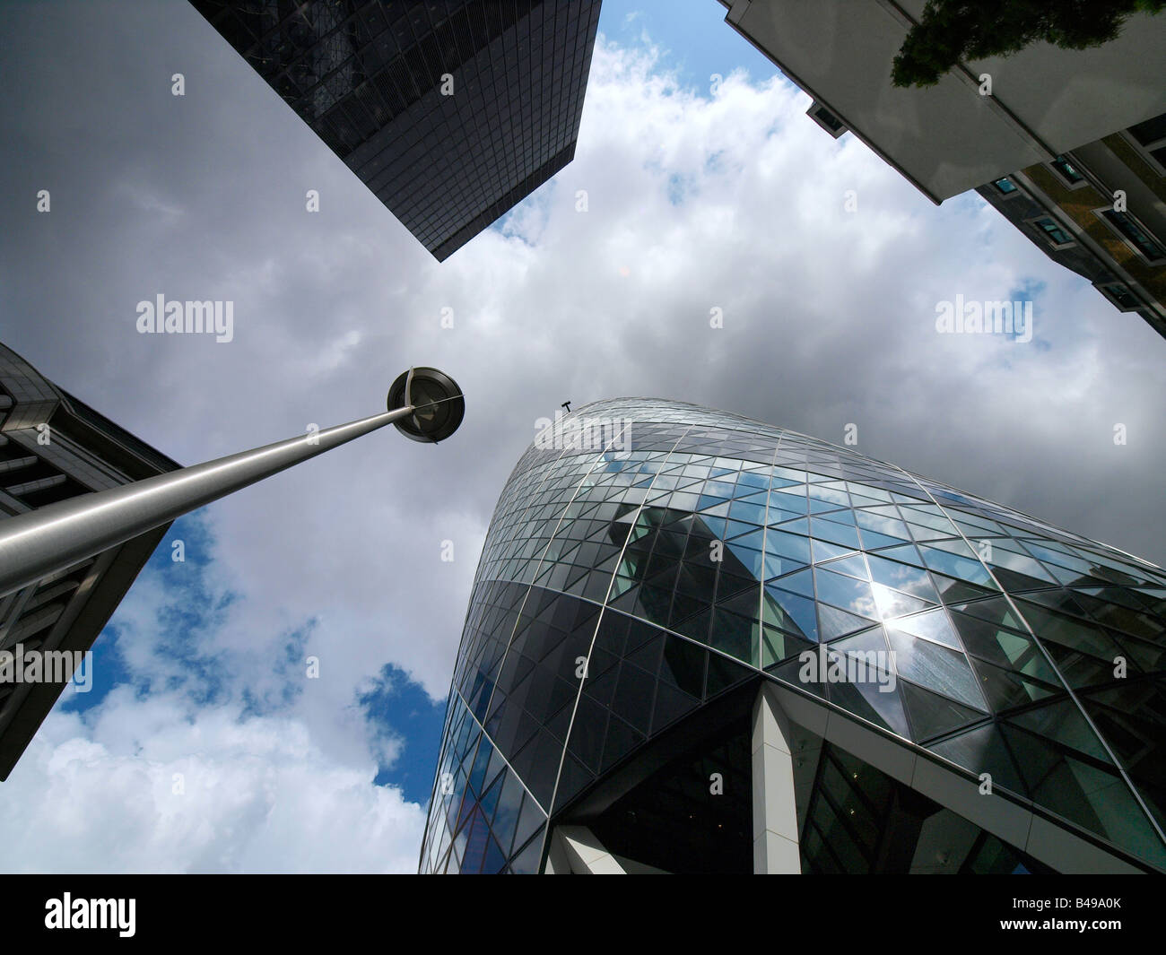 Looking up in the London City dynamic image with Gherkin building and nice clouds - Stock Image