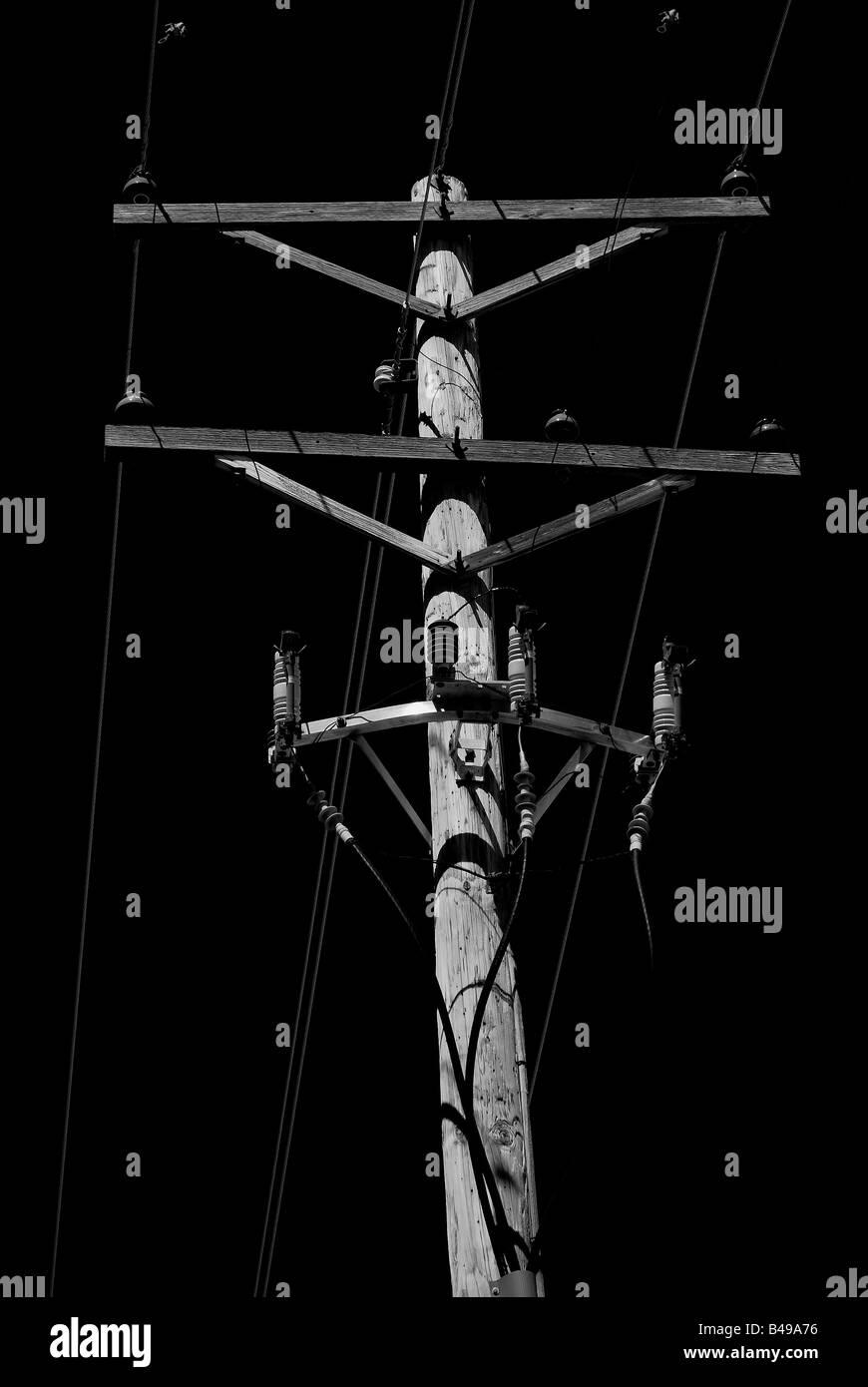 A Telephone Pole against a black sky - Stock Image