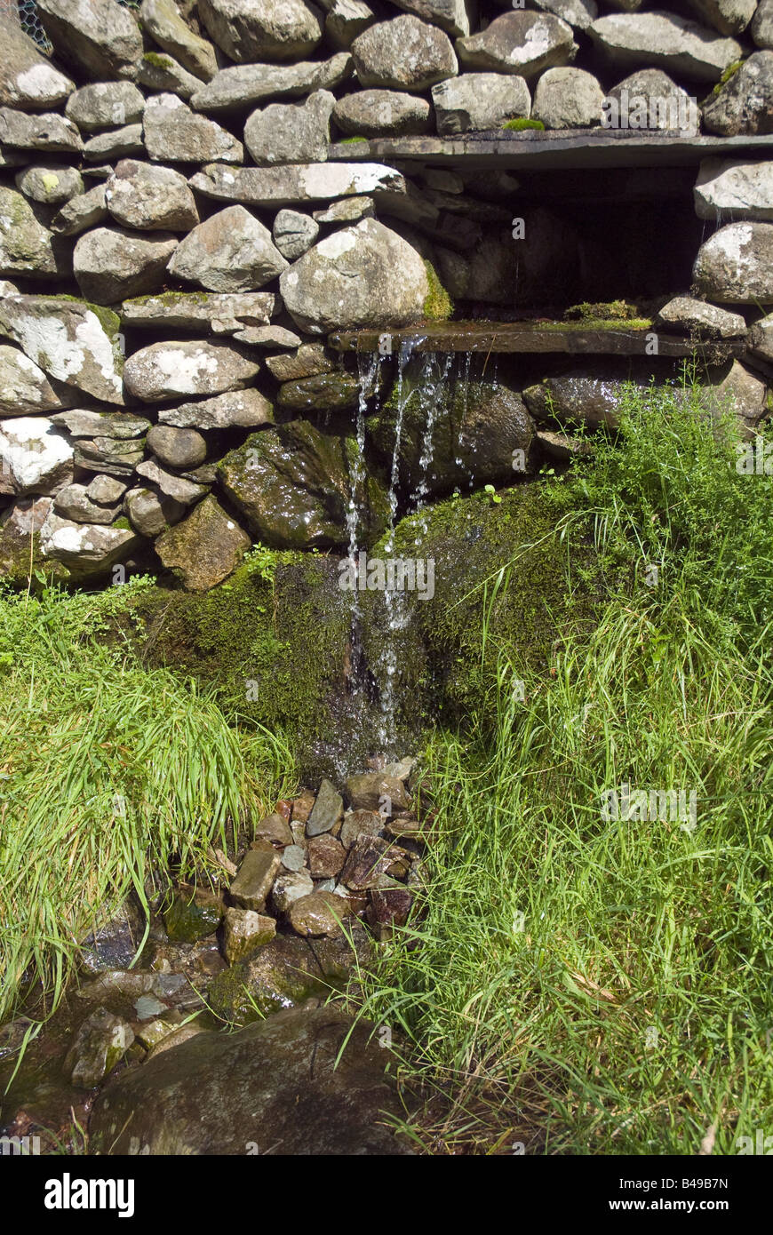 A lake district stream trickles through a grey slate wall. - Stock Image