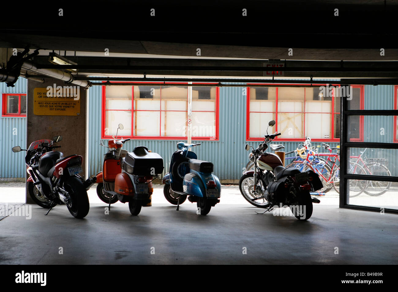 motor scooter and motor cycles parked in a garage - Stock Image