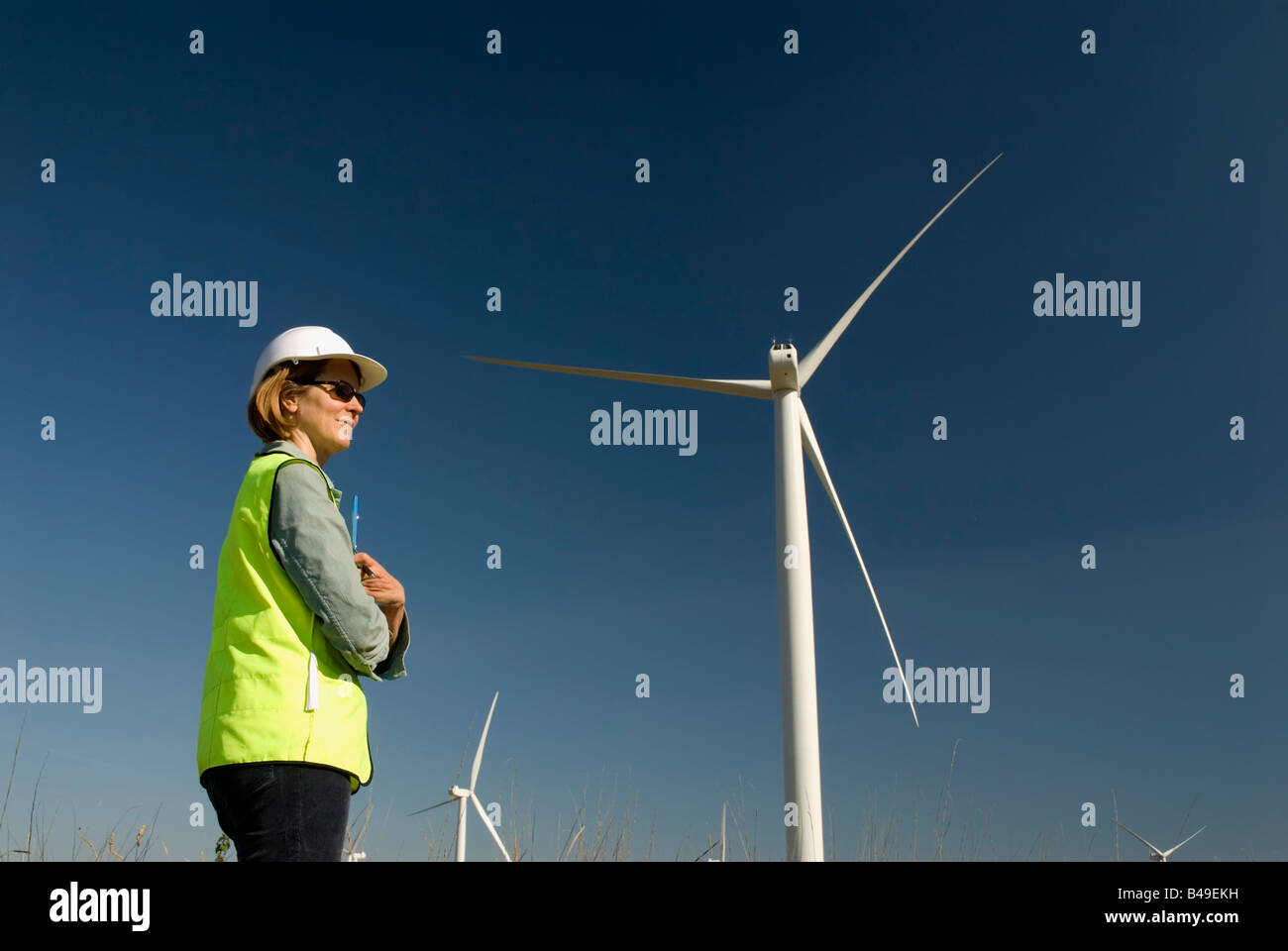Female engineer green collar jobs next to wind turbine wind farm - Stock Image