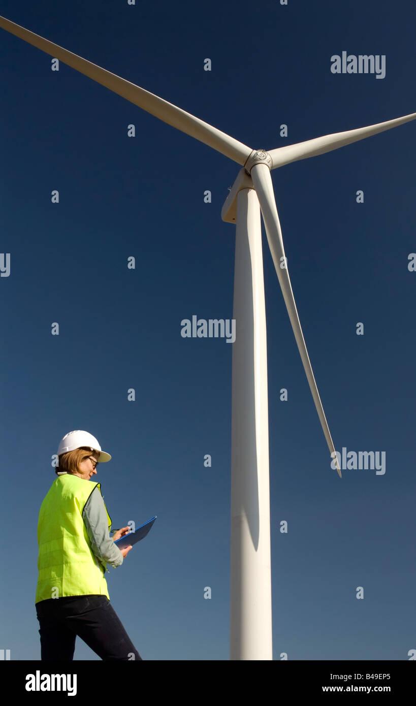 Female engineer next to wind turbine wind farm - Stock Image
