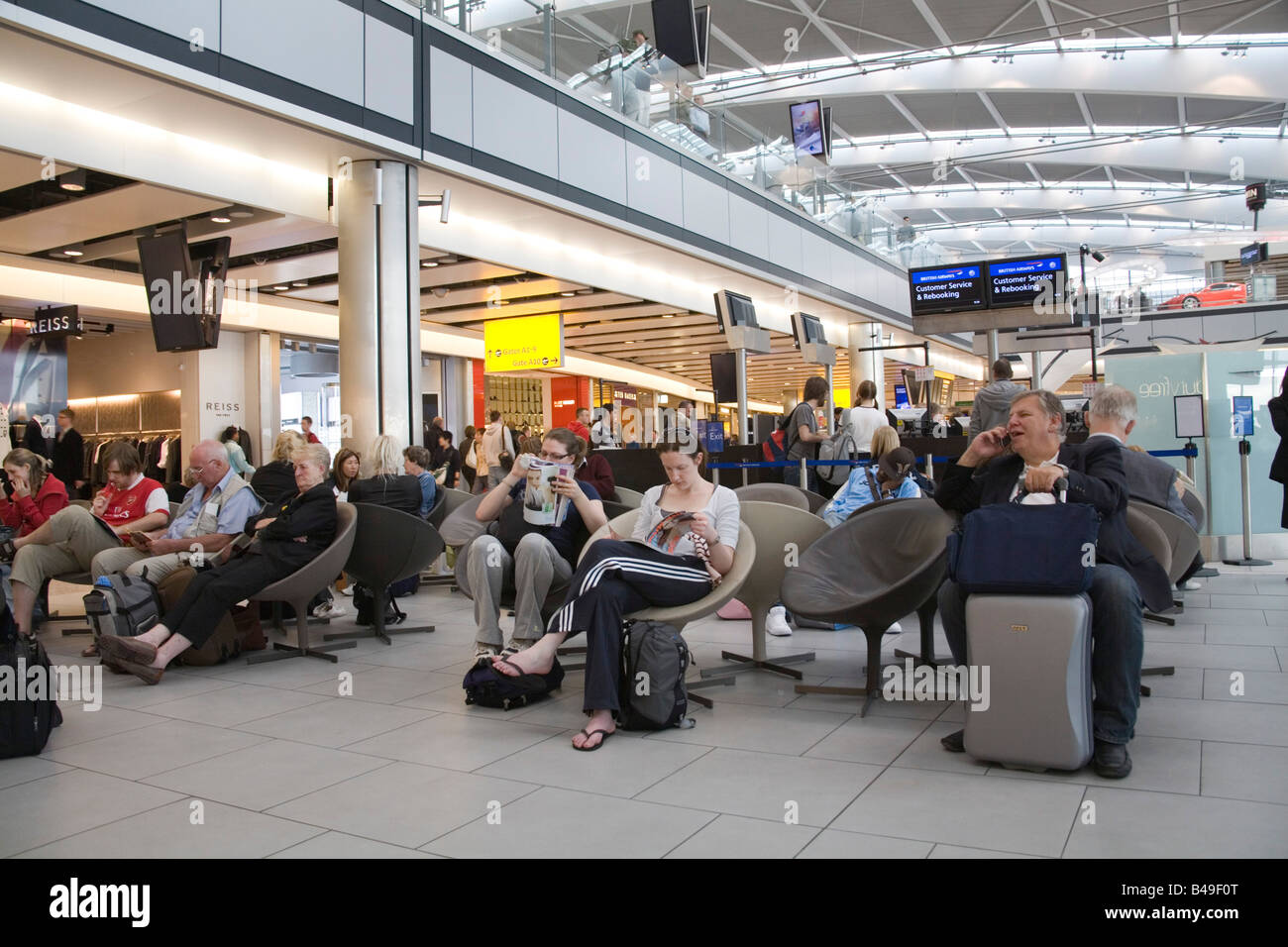 Heathrow Airport London England UK September Businessman on a mobile phone waiting in Departure Lounge of Terminal - Stock Image