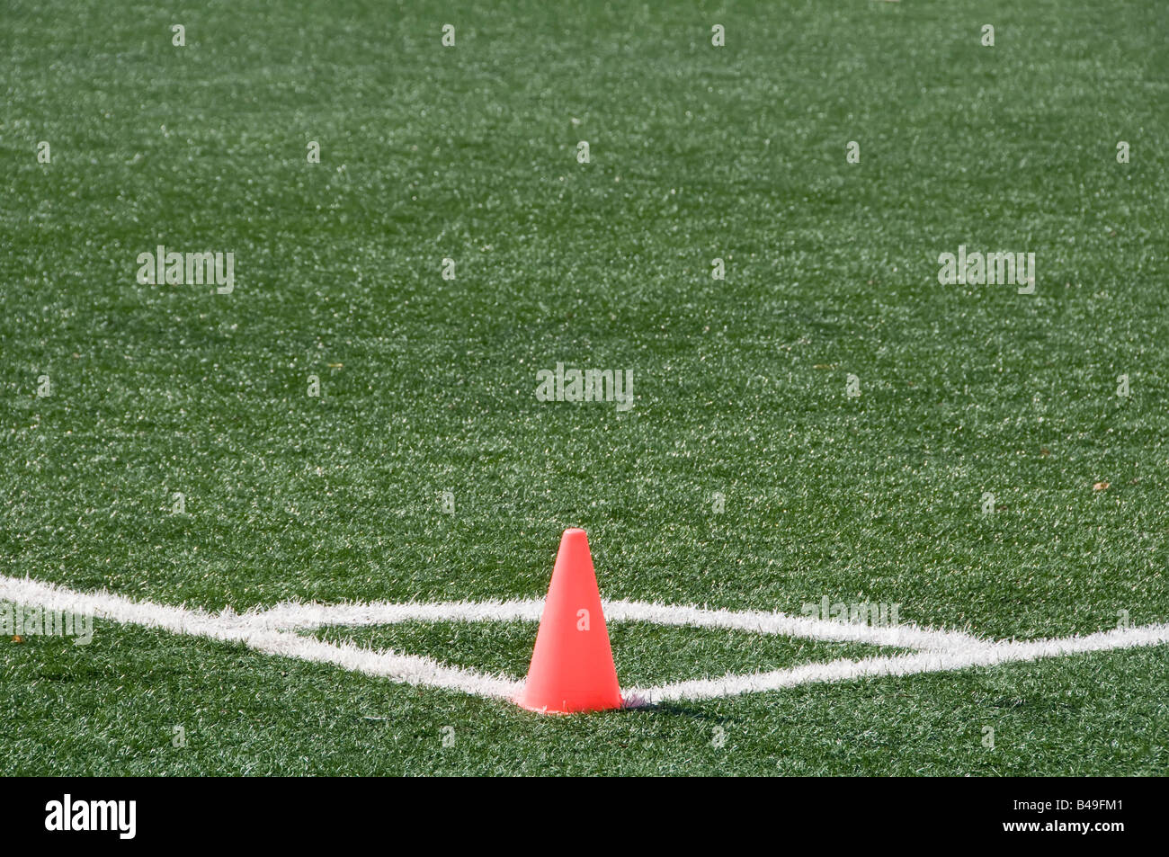 Pink cone standing at corner of football soccer field - Stock Image