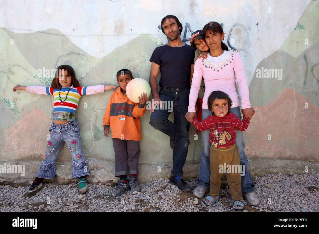 Roma gypsy family standing in front of a mural next to their home in Korca, Albania - Stock Image