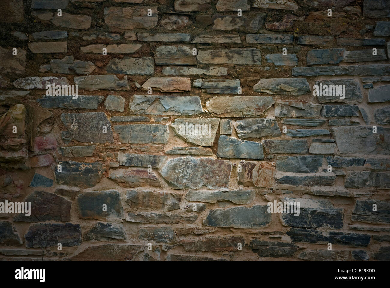 an old dirty and grungy stone wall background - Stock Image