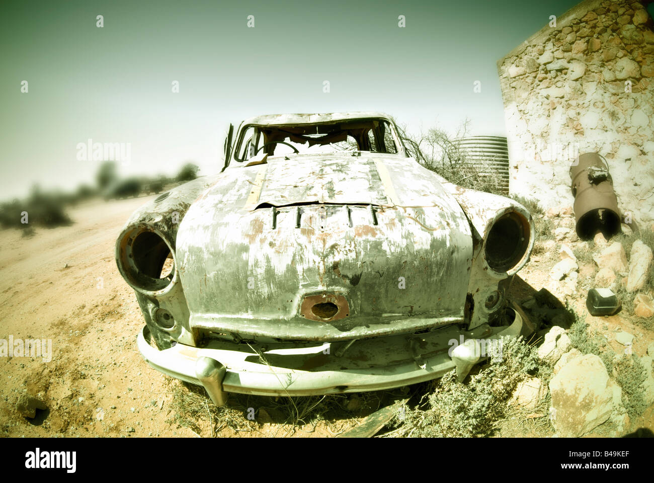 cross processed image of an old car in the desert - Stock Image