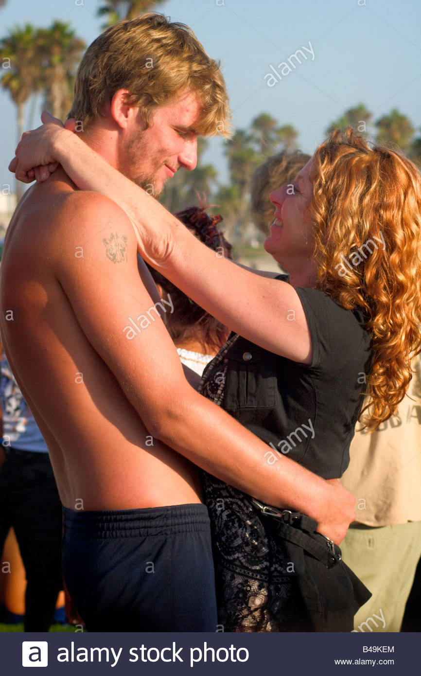 Young Adult Couple Embracing During Drum Circle Dance Venice Beach Caliifornia - Stock Image