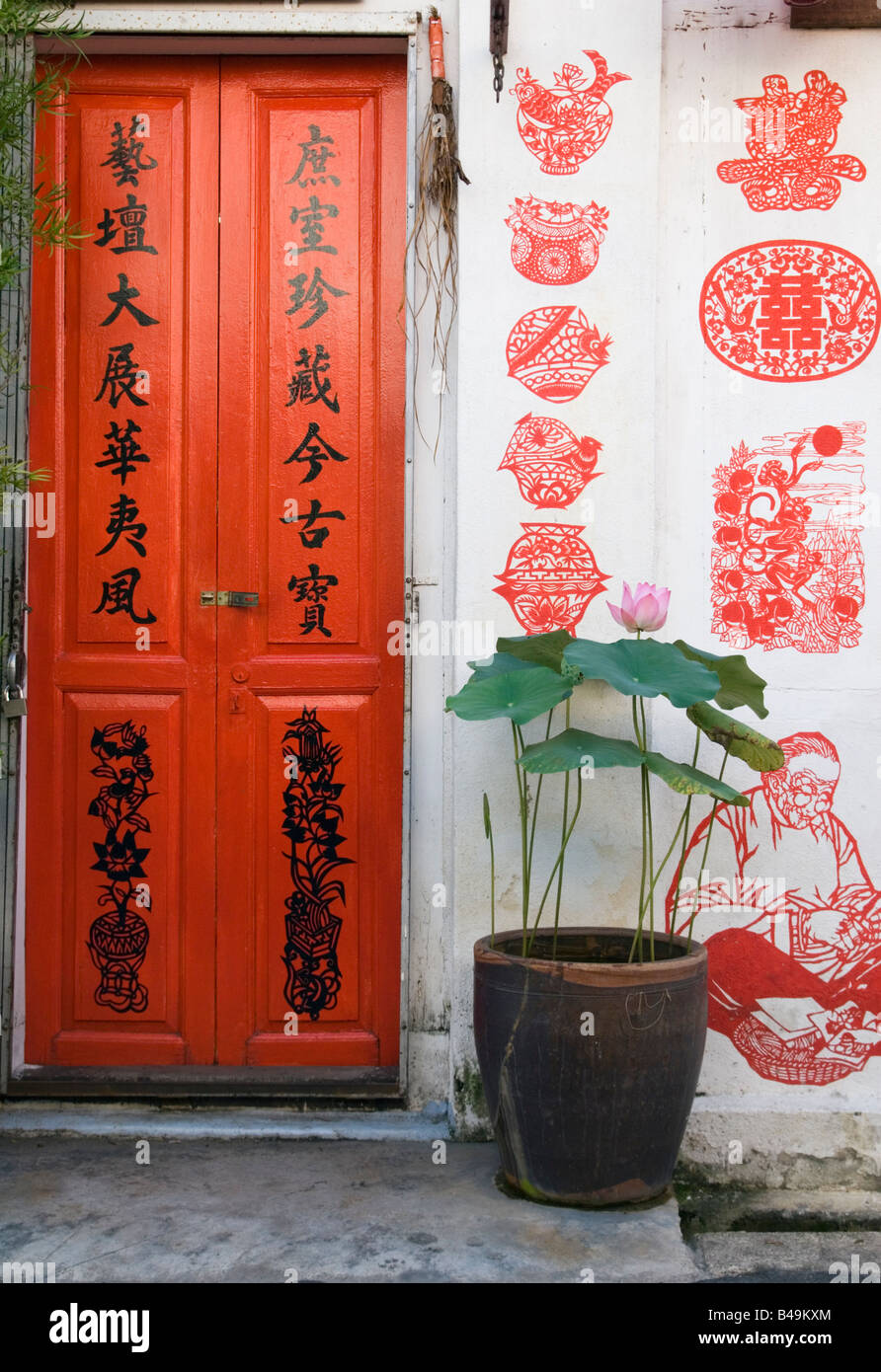 Chinatown detail with double red doors and characters painted on the exterior walls behind a lotus plant in Malacca, - Stock Image
