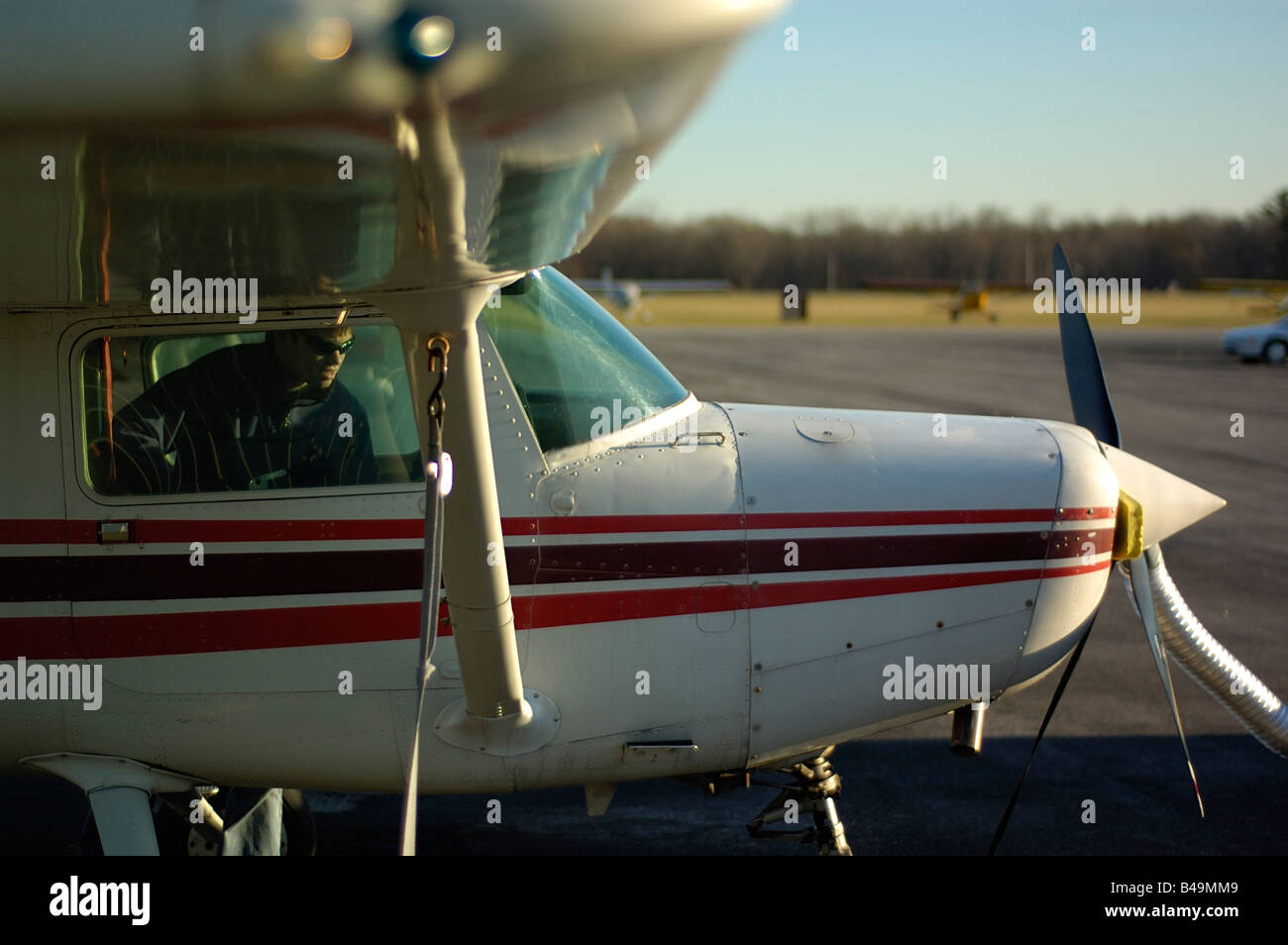 Pilot performs preflight check on a small single engine aircraft while the engine is preheated prior to take off - Stock Image