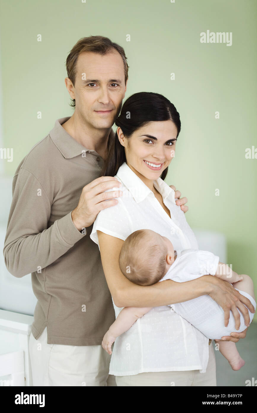 Parents smiling at camera, woman holding baby, portrait Stock Photo