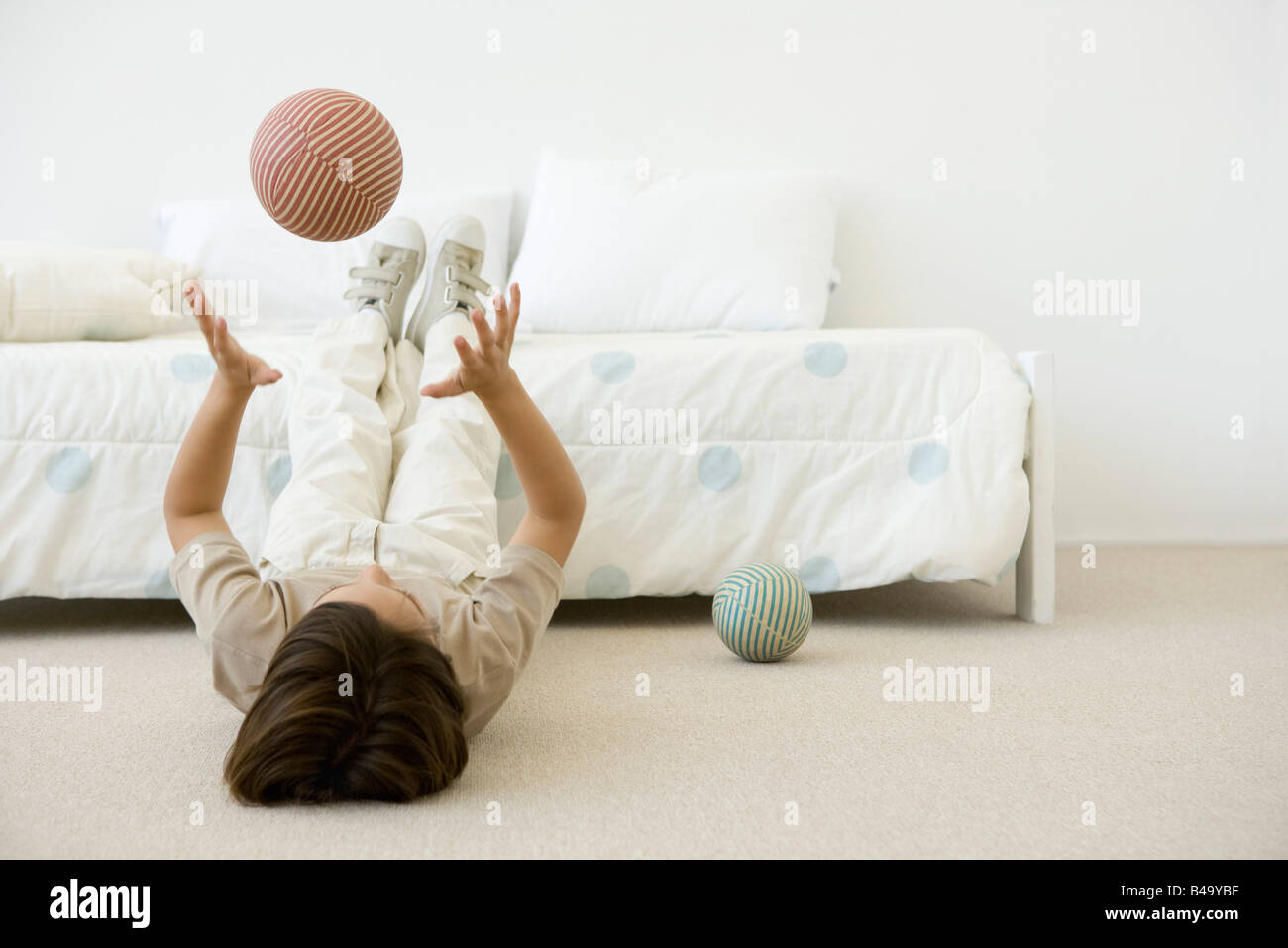 Boy lying on the ground in bedroom, throwing ball in the air - Stock Image